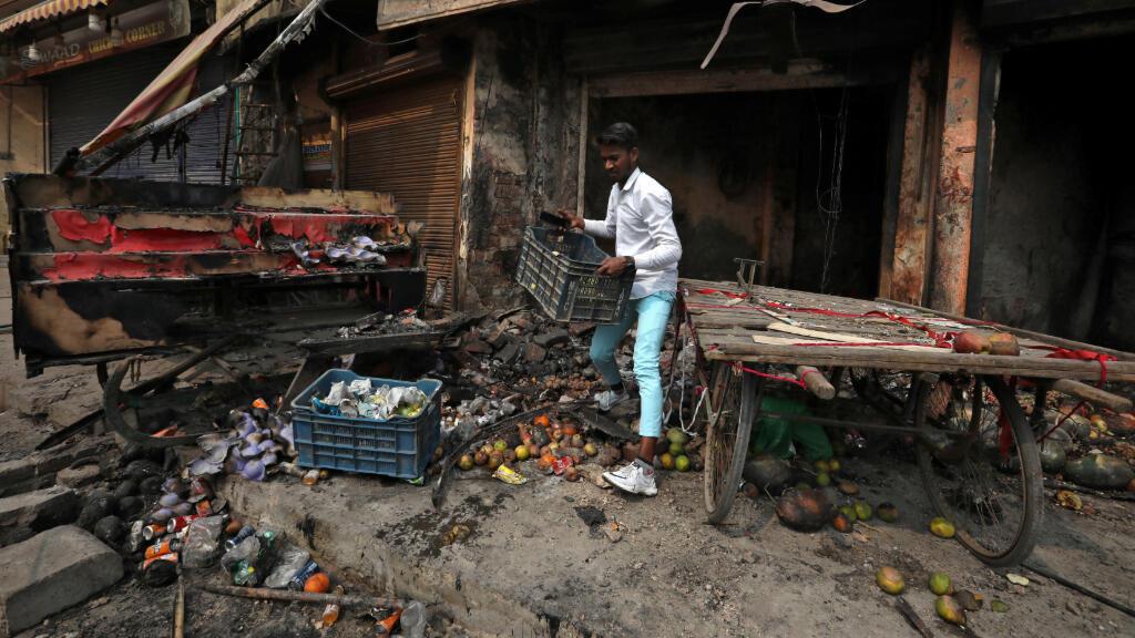 Un vendedor rescata las pertenencias de su tienda, incendiada después de que estallaran los enfrentamientos entre los a favor y los en contra de la nueva ley de ciudadanía en Nueva Delhi, el 26 de febrero.