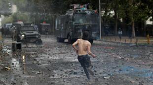Un manifestante arroja una piedra a los vehículos de la policía antidisturbios durante una nueva protesta contra el gobierno de Chile en Santiago, el 4 de noviembre de 2019.