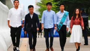 Joshua Wong, centro, camina con un grupo de sus compañeros hacia una rueda de prensa para denunciar el veto que le impide ser candidato en las elecciones del Consejo de Distrito de Hong Kong. 29 de octubre de 2019.