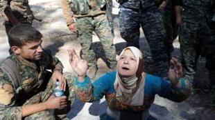 Una mujer ora tras ser rescatada del estadio de Raqa, liberada del 'Estado Islámico'. Siria, octubre 17, 2017