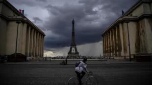 رجل يقود دراجة قرب برج إيفل في باريس في 9 أيار/مايو 2020