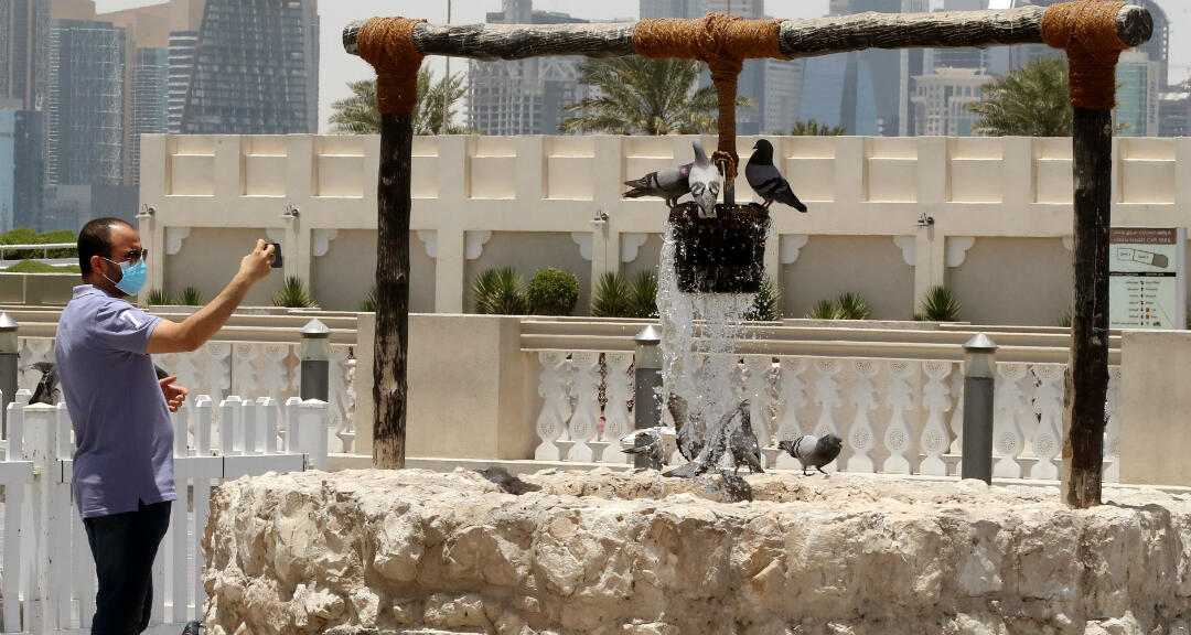 Un hombre lleva una mascarilla mientras toma foto a unos pájaros en una fuente en Doha, Catan, el 17 de mayo de 2020.