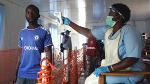 Un trabajador de salud verifica la temperatura de un hombre mientras cruza el punto fronterizo de Mpondwe, que separa a Uganda y la República Democrática del Congo, como parte de la prueba de ébola en el Centro de Evaluación de la Salud de Mpondwe, Uganda, el 13 de junio de 2019.