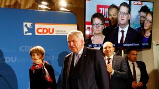 La principal candidata de la Unión Demócrata Cristiana (CDU) y el Primer Ministro del Estado de Hesse pasan al lado de una pantalla de televisión que muestra al principal candidato del Partido Socialdemócrata (SPD), Thorsten Schaefer-Guembel, tras las elecciones en el estado de Hesse en Wiesbaden, Alemania, el 28 de octubre de 2018.