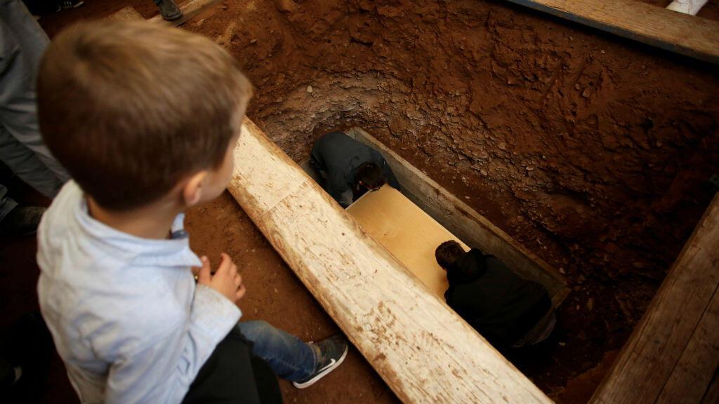 Un niño mira cómo sus familiares entierran uno de los ataúdes durante el funeral de Rhonita Miller LeBaron, y sus hijos.
