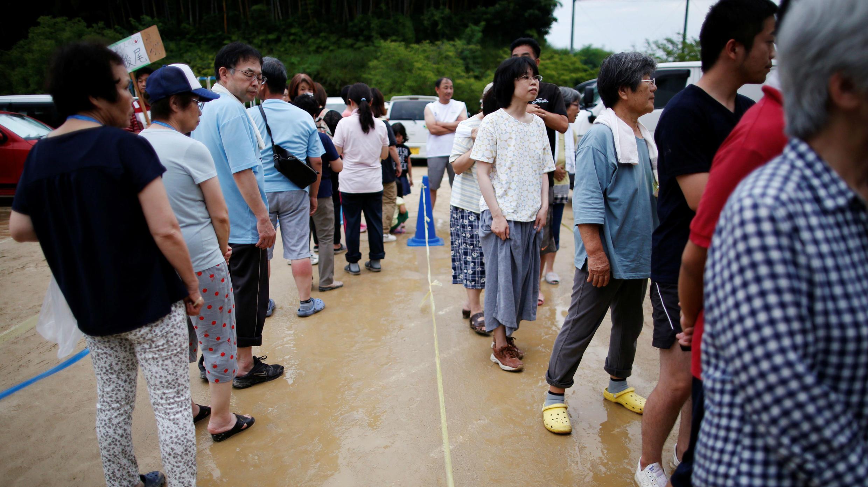 Los evacuados hacen fila para recibir un suministro de alimentos en la escuela primaria de Okada, que actúa como centro de evacuación en la ciudad de Mabi, en Kurashiki, Prefectura de Okayama, Japón, el 12 de julio de 2018.