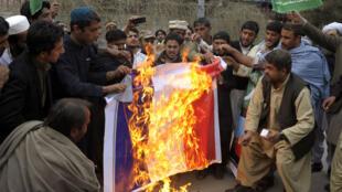 """Des Pakistanais brûlent un drapeau français, vendredi 16 janvier, lors de la manifestation contre """"Charlie Hebdo""""."""