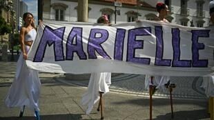 Women walk on stilts while holding a banner in memory of Rio councillor Marielle Franco, at the location in Rio de Janeiro where she was shot dead