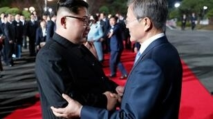 North Korea's leader Kim Jong Un (L) and South Korea's President Moon Jae-in agreed plans for a liaison office at their summit in April