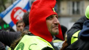 Un Gilet jaune, portant un bonnet phrygien, attend le départ d'une des manifestations organisées à Paris, samedi 4 mai 2019.