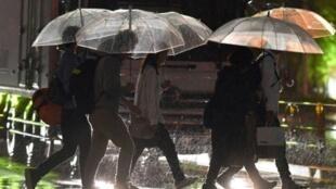 أشخاص يحتمون من المطر الغزير الناجم عن الإعصار تاليم، في طوكيو الاثنين 17 أيلول/سبتمبر 2017