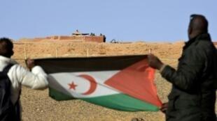صحراويان يرفعان علم البوليساريو في منطقة المحبس أمام جنود مغاربة ينتشرون عند الحائط الذي يفصل المغرب عن الجهة التي تسيطر عليها بوليساريو في الصحراء الغربية، في 3 شباط/فبراير 2017