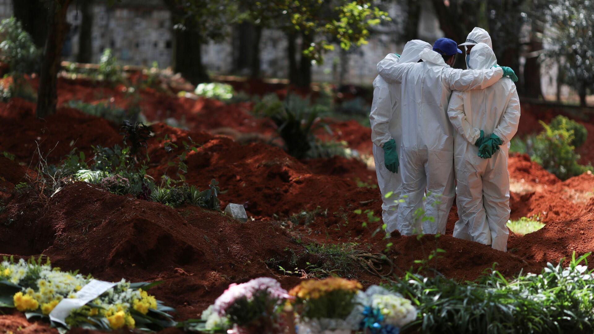 Sepultureros con trajes protectores se reúnen en el cementerio de Vila Formosa, el cementerio más grande de Brasil, durante el brote de la enfermedad por coronavirus (COVID-19), en Sao Paulo