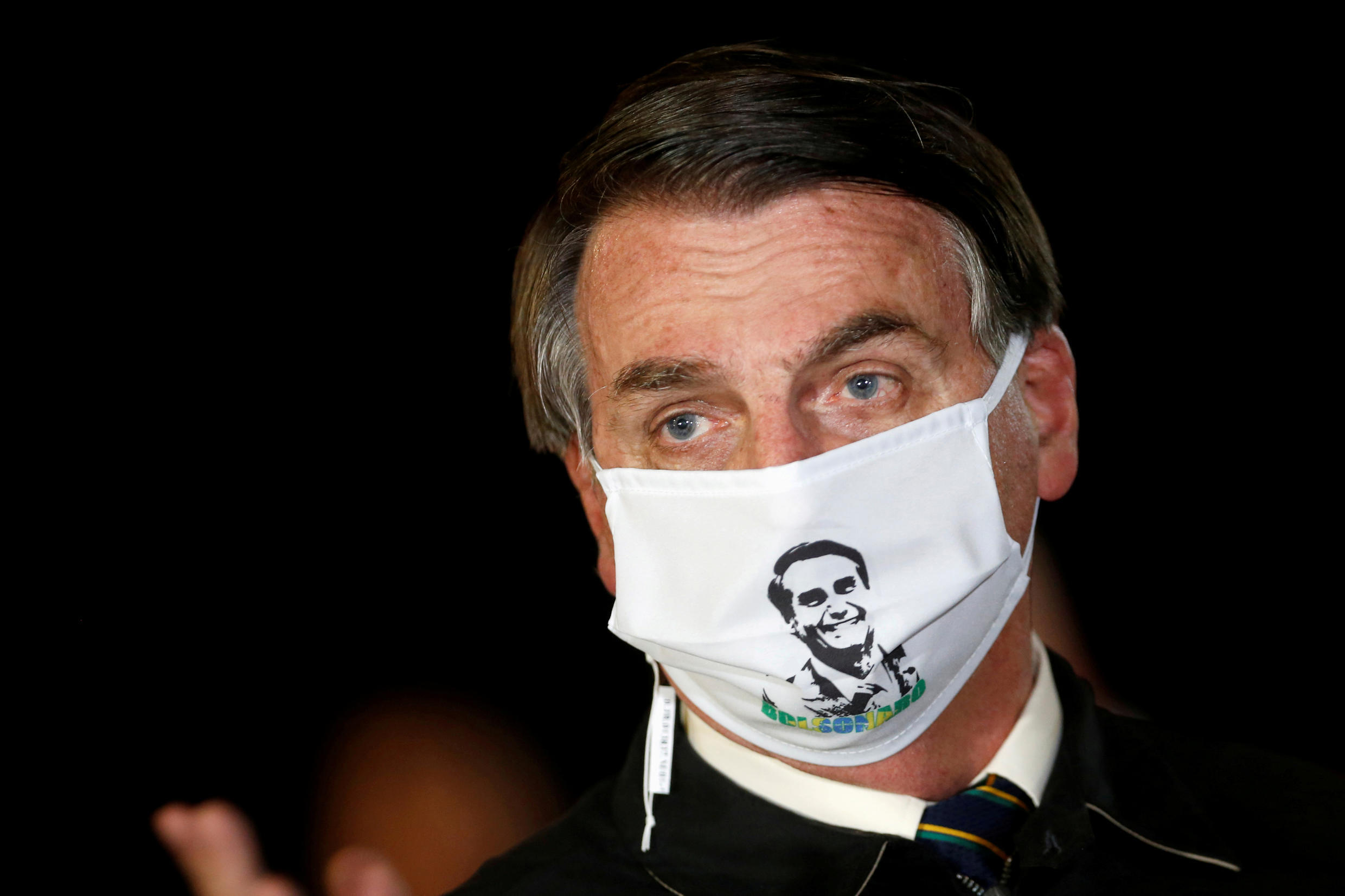 Brazil's President Jair Bolsonaro speaks with journalists while wearing a protective face mask as he arrives at Alvorada Palace, amid the coronavirus disease (COVID-19) outbreak, in Brasilia, Brazil, May 22, 2020.
