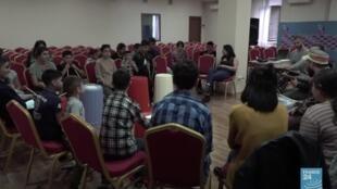 Des bénévoles organisent des ateliers de chants avec de jeunes déplacés au Centre Nexus pour les Arts.