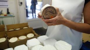 Une employée de la fromagerie Durand, le 24 août 2016, emballe un camembert au lait cru.