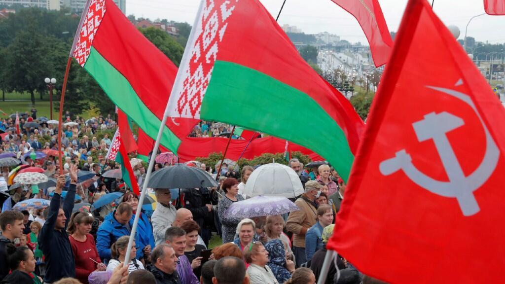 Varias personas portan la bandera oficial bielorrusa junto a otra de la Unión Soviética durante una de las manifestaciones en apoyo de Alexander Lukashenko. En Minsk, Belarús, el 19 de agosto de 2020.