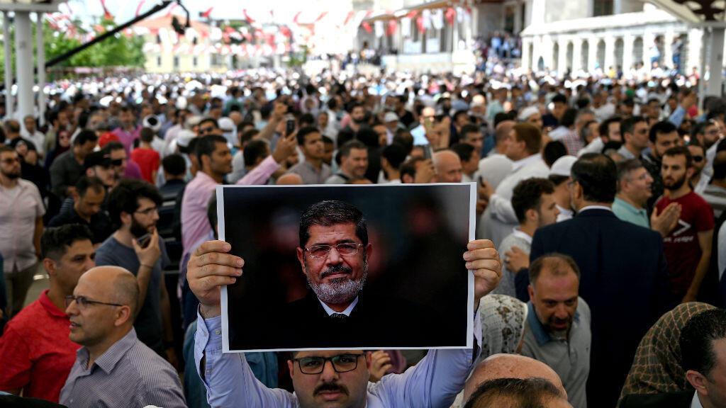 Un hombre sostiene una foto del presidente egipcio Mohamed Morsi durante una ceremonia simbólica el 18 de junio de 2019 en la mezquita de Fatih en Estambul.