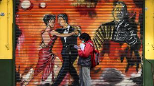 رجل يضع كمامة أمام رسم جداري يظهر راقصي تانغو في بوينوس ايرس بتاريخ 8 أيار/مايو 2020
