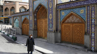 A woman wearing a protective face mask and gloves walks past the Imamzadeh Saleh shrine in Tehran, Iran, on April 2, 2020.