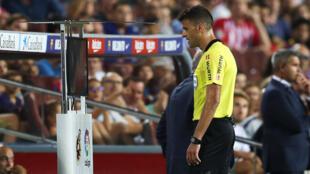 El árbitro Gil Manzano observa las imágenes del VAR, durante un partido de liga española entre Barcelona y el Girona, el 23 de septiembre de 2018.
