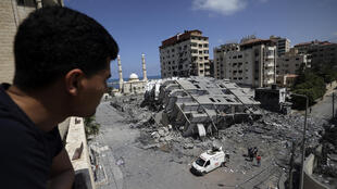 A Palestinian looks at a destroyed building in Gaza City, following a series of Israeli airstrikes on the Gaza Strip early on May 12