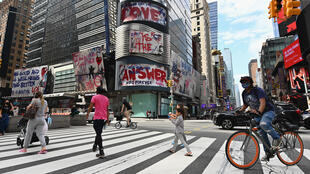 People cross the street near Time Square in New York City, which now faces potential re-imposition of virus restrictions in some neighborhoods