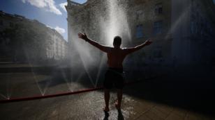 Un hombre se refresca en uno de los rociadores de agua instalados en Viena, Austria. 23 de julio de 2019.
