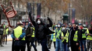 متظاهر يلقي كرسيا في جادة الشانزليزيه في باريس 24 تشرين الثاني/نوفمبر 2018