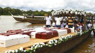 Familiares transportan este lunes 11 de noviembre por el río Atrato (Colombia), los restos de las víctimas de la masacre de Bojayá ocurrida en 2002.