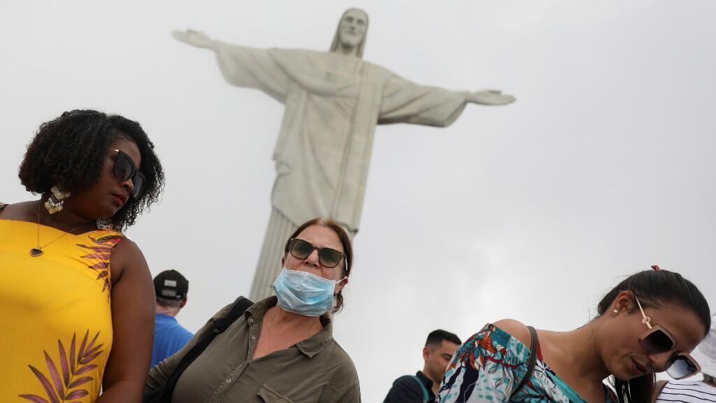 Una turista lleva una máscara protectora, entre temores de coronavirus, mientras visita la estatua del Cristo Redentor en Río de Janeiro, Brasil, el 14 de marzo de 2020.