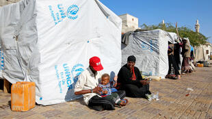 Des Yéménites déplacés par la guerre dans le nord-ouest du pays sont assis devant leur abri de fortune dans la ville portuaire de Hodeïda, le 25 décembre 2017.