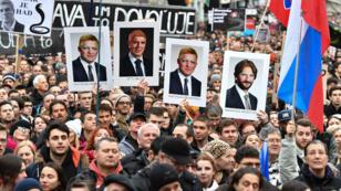 Des manifestants brandissent des pancartes montrant des membres du gouvernement grimés, lors d'un rassemblement anticorruption, le 16 mars 2018 à Bratislava.