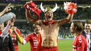 Casque viking sur la tête, l'attaquant danois Andreas Cornelius célèbre la qualification de son pays à la Coupe du monde après avoir battu l'Irlande à Dublin, le 14 novembre 2017.