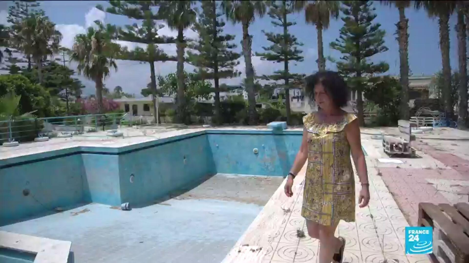 Valentini Troumouzi walks by the empty hotel pool where she used to serve tourists on the Greek island of Kos.