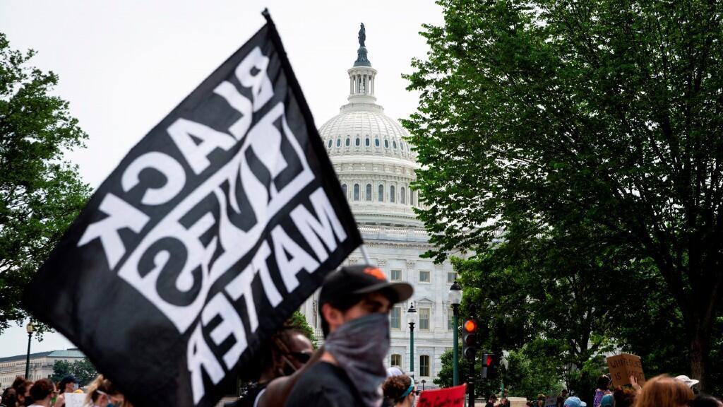"""Un manifestante con un cartel que reza """"las vidas negras importan"""" marcha frente a la Casa Blanca en Washington D. C., Estados Unidos, el 6 de junio de 2020."""