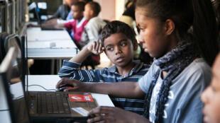 Des enfants malgaches âgés de 7 à 13 ans apprennent à coder sur un ordinateur à l'initiative de l'ONG Habaka.