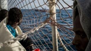 مهاجرون على متن السفينة سي ووتش 3 وقبالتهم سفينة لخفر السواحل الإيطالي