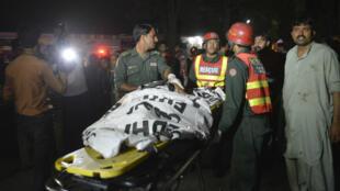 Des secouristes pakistanais portent un corps après l'explosion qui a frappé Lahore, au Pakistan, le 27 mars 2016.