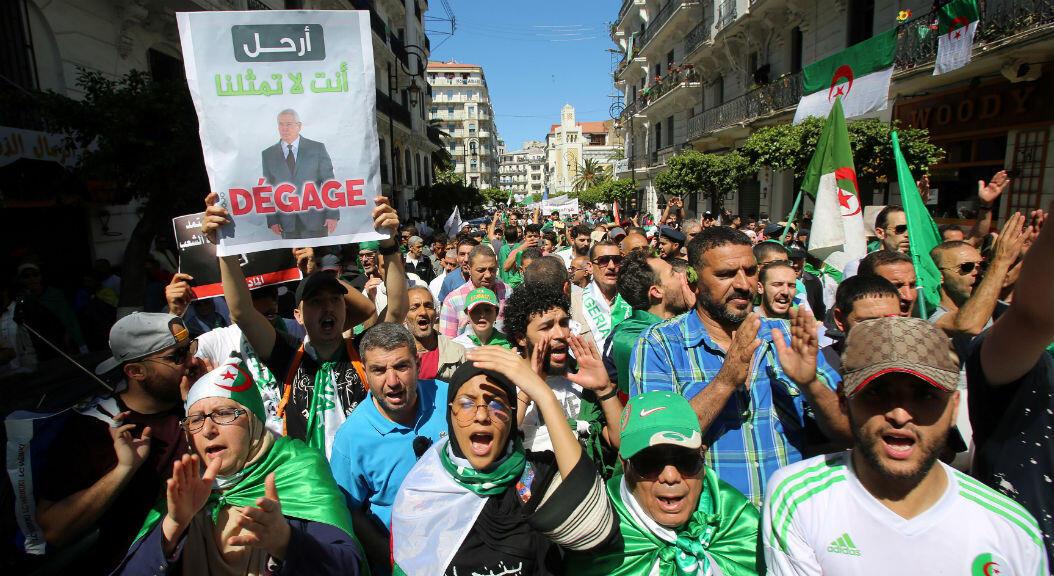 Un grupo de manifestantes sostiene la foto del presidente interino de Argelia,Abdelkader Bensalah,mientras piden un cambio radical de gobierno.