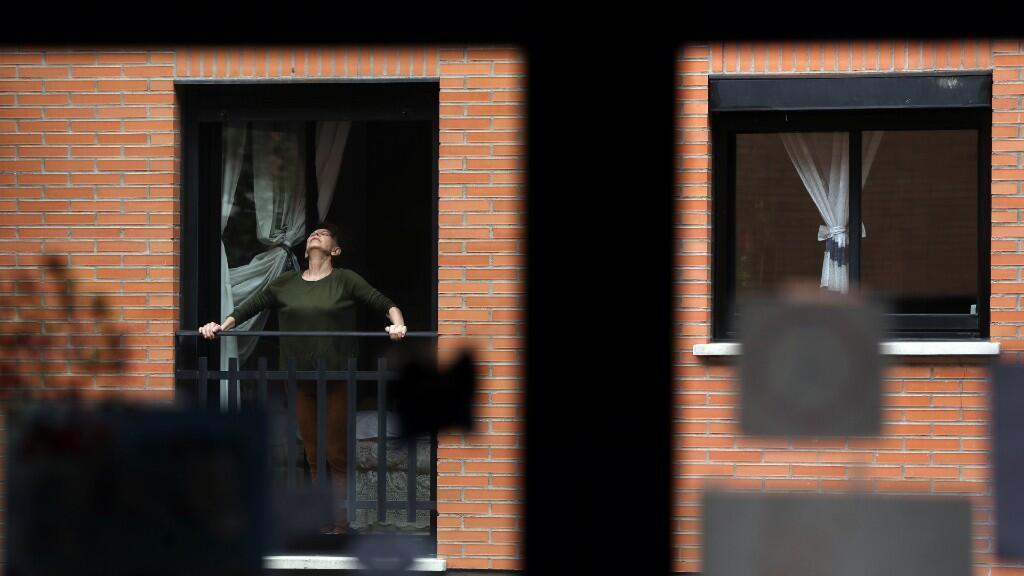 Una mujer realiza estiramientos en su balcón en Madrid, durante el aislamiento que vive España por estos días. 11 de abril de 2020.
