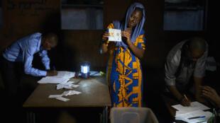 Una funcionaria electoral muestra una papeleta durante el recuento de votos en una mesa electoral en Bamako, después de la segunda vuelta de las elecciones presidenciales de Mali. 12 de agosto de 2018.