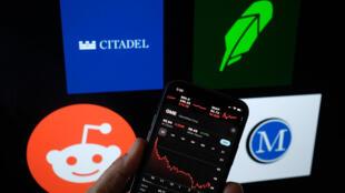 Un gráfico de la acción de GameStop en la pantalla de un celular, el 17 de febrero de 2021, frente a los logos de las aplicaciones de Reddit, Citadel, Robinhood y Melvin Capital