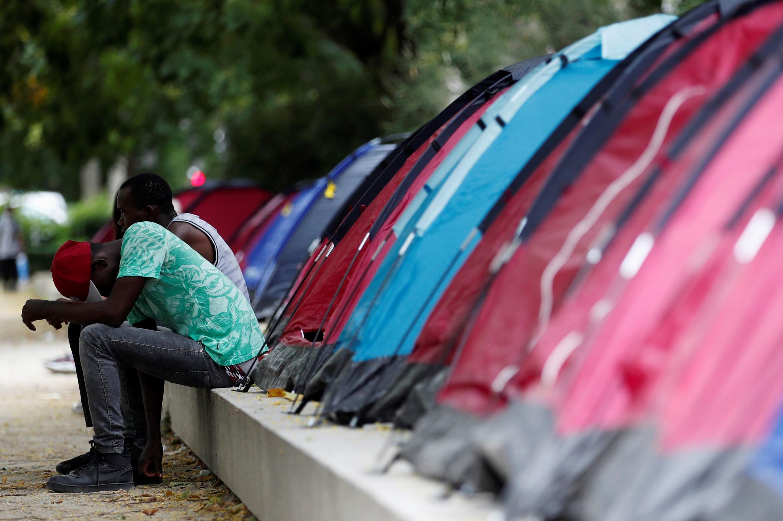 مهاجرون يجلسون بالقرب من مخيّم بشمال باريس، فرنسا، 30 يونيو  2020.