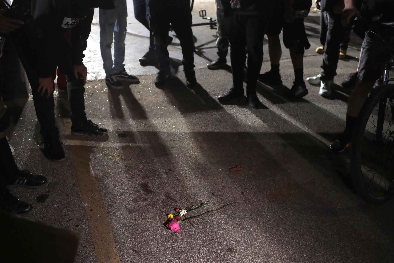 Los manifestantes se reúnen alrededor de un pequeño monumento en el lugar donde uno de los manifestantes antirracistas fue asesinado en la noche del 25 al 26 de agosto en Kenosha, Wisconsin por un miliciano.