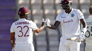 West Indies captain Jason Holder (R) celebrates with John Campbell (L) after a four-wicket win over England in the first Test at Southampton