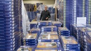 Eric Lathière-Lavergne, patron de Planet'Puzzles, pose devant une pile de puzzles dans ses locaux de Behren-lès-Forbach, le 11 février 2021