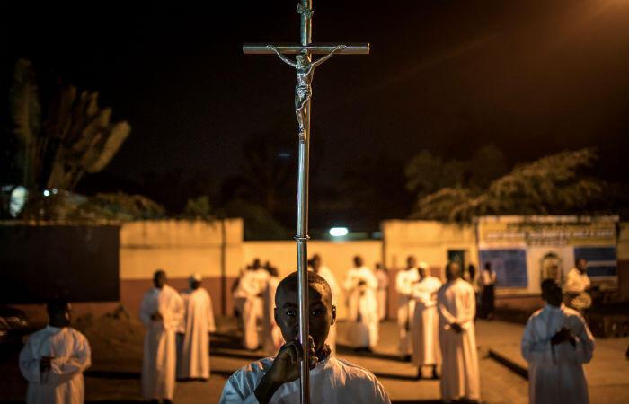 De jeunes fidèles se préparent à défiler devant la cathédrale Notre-Dame de Kinshasa, le 24 décembre 2018, au début des célébrations de la messe de Noël.