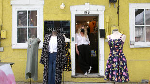 Boutique owner Pat Phythian stands in the doorway of her as she waits for customers Ottawa, Ontario, as Canada's most populous province allows stores with street access to reopen after two months of coronavirus lockdown