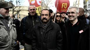 """Le secrétaire général de la Confédération générale du travail(CGT), Philippe Martinez (au centre), et le secrétaire général de Force ouvrière(FO), Yves Veyrier (à droite), lors de la """"Journée des grèves"""" organisée le 19mars2019."""